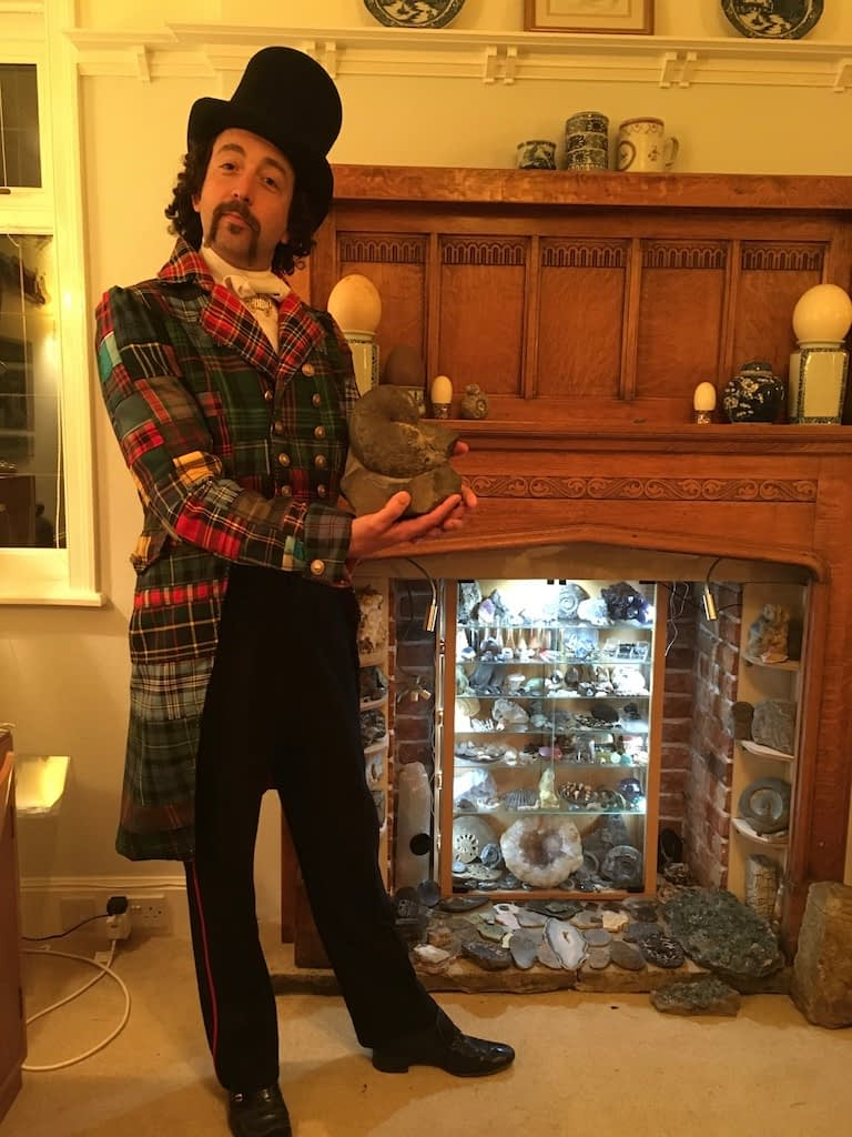 Dressed in a tartan patchwork tailcoat, The Rock Showman holds an ammonite fossil in front of a rock collection