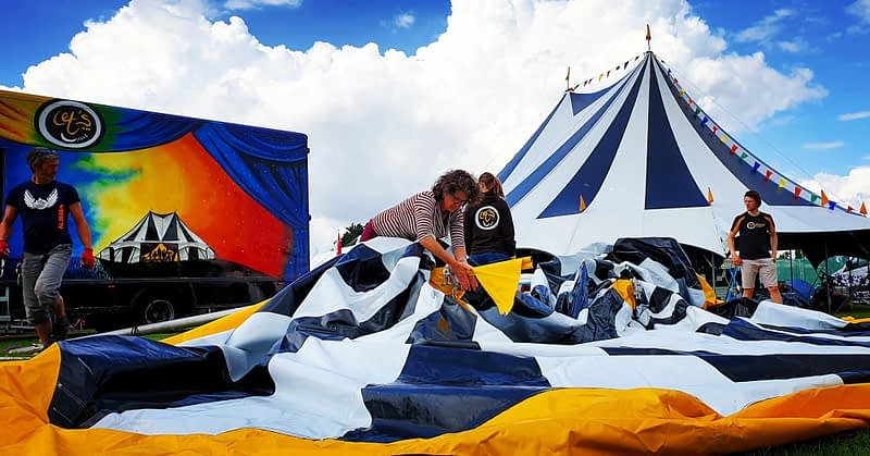 Let's Circus team members build their colourful circus tents for a festival zone.